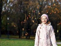Adolescente que juega con las hojas otoñales Foto de archivo