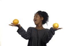 Adolescente que juega con las naranjas Imagenes de archivo