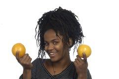 Adolescente que juega con las naranjas Foto de archivo