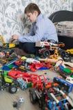 Adolescente que juega con los coches del juguete en sitio Fotografía de archivo