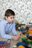 Adolescente que juega con los coches del juguete en sitio Fotos de archivo