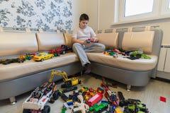 Adolescente que juega con los coches del juguete en sitio Foto de archivo libre de regalías