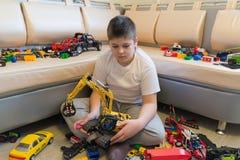 Adolescente que juega con los coches del juguete en sitio Imagenes de archivo