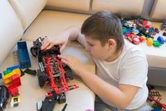 Adolescente que juega con los coches del juguete en sitio Imagen de archivo