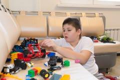 Adolescente que juega con los coches del juguete en sitio Foto de archivo