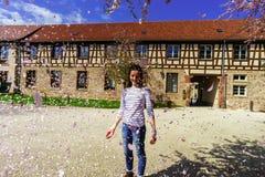 Adolescente que juega con los pétalos que caen en el sol Imagen de archivo