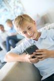 Adolescente que juega con smartphone en casa Foto de archivo