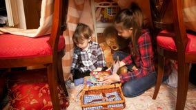 Adolescente que juega con su pequeño hermano en tienda en el dormitorio Fotos de archivo libres de regalías