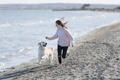 Adolescente que juega con su perro en una playa Imágenes de archivo libres de regalías