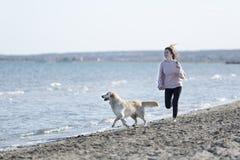 Adolescente que juega con su perro en una playa Foto de archivo