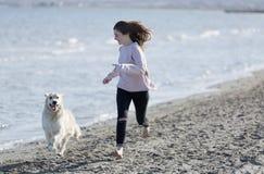 Adolescente que juega con su perro en una playa Fotos de archivo