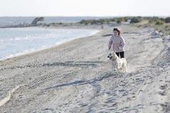 Adolescente que juega con su perro en una playa Fotografía de archivo libre de regalías