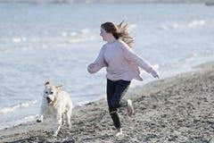Adolescente que juega con su perro en una playa Foto de archivo libre de regalías