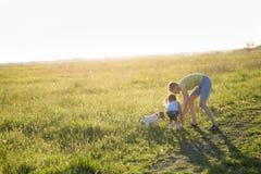 Adolescente que juega con un perro en la naturaleza, Imagen de archivo