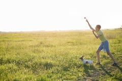 Adolescente que juega con un perro en la naturaleza, Foto de archivo libre de regalías