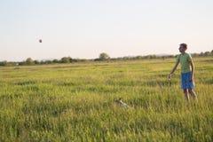 Adolescente que juega con un perro en la naturaleza, Imagen de archivo libre de regalías