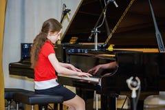 Adolescente que juega el piano de cola Imagen de archivo libre de regalías