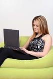 Adolescente que juega en el ordenador portátil Fotografía de archivo libre de regalías