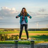 Adolescente que juega en el patio de los niños, igualando Imagen de archivo libre de regalías