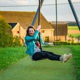 Adolescente que juega en el patio de los niños, igualando Fotografía de archivo