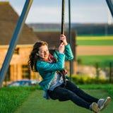 Adolescente que juega en el patio de los niños, igualando Fotografía de archivo libre de regalías