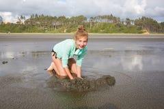 Adolescente que juega en la arena mojada Imagen de archivo