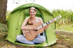 Adolescente que juega en la guitarra cerca de la tienda Fotografía de archivo