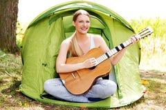 Adolescente que juega en la guitarra cerca de la tienda Imagen de archivo libre de regalías