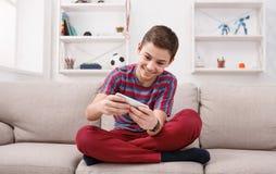 Adolescente que juega a juegos en smartphone Imagenes de archivo