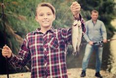 Adolescente que lanza la captura en pescados del gancho Imágenes de archivo libres de regalías