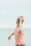 Adolescente que lanza piedras en el mar Fotografía de archivo libre de regalías