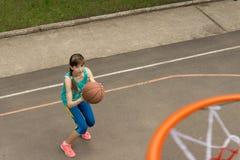 Adolescente que lanza un baloncesto en la red Imagen de archivo