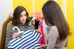 Adolescente que le muestra la ropa a su novia Imagen de archivo libre de regalías