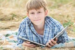 Adolescente que lee el libro grande Imagen de archivo libre de regalías
