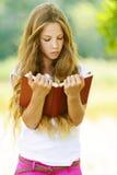 Adolescente que lee el libro rojo Imagen de archivo libre de regalías