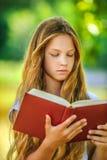 Adolescente que lee el libro rojo Imagenes de archivo