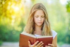 Adolescente que lee el libro rojo Imagen de archivo