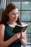 Adolescente que lee su biblia en casa Fotos de archivo