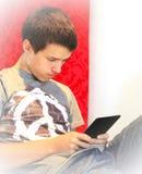 Adolescente que lee un eBook Imagenes de archivo