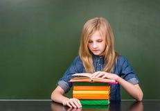 Adolescente que lee un libro cerca de la pizarra verde vacía Imagenes de archivo