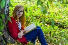Adolescente que lee un libro en bosque Imagen de archivo