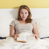 Adolescente que lee un libro en cama Fotos de archivo libres de regalías