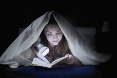 Adolescente que lee un libro en cama bajo cubiertas Fotos de archivo libres de regalías