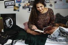 Adolescente que lee un libro en un dormitorio Fotos de archivo libres de regalías