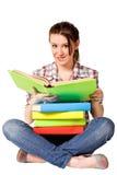 Adolescente que lee un libro en el suelo Fotos de archivo