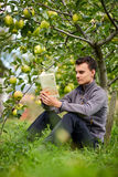 Adolescente que lee un libro en la huerta Foto de archivo libre de regalías