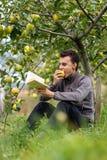 Adolescente que lee un libro en la huerta Imágenes de archivo libres de regalías