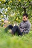 Adolescente que lee un libro en la huerta Imagenes de archivo