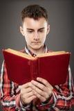 Adolescente que lee un libro viejo Imagen de archivo libre de regalías