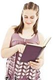 Adolescente que lee un libro y una sonrisa Imagen de archivo libre de regalías